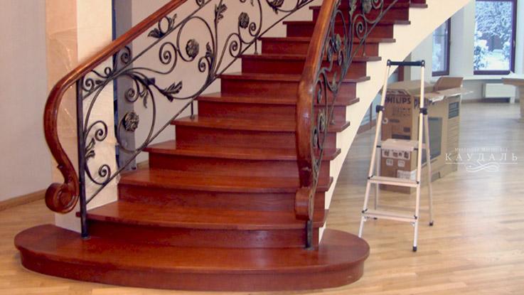 Лестница на заказ с кованными перилами и деревянными поручнями.