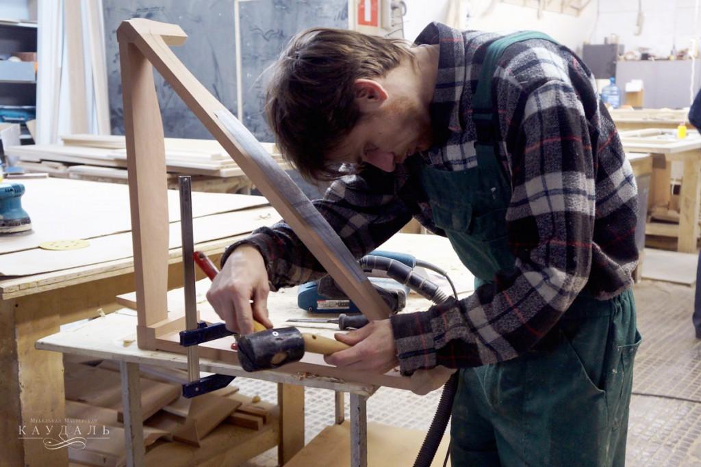 Столяр в мастерской вырезает узор
