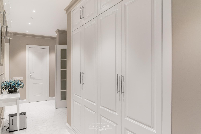 Белый шкаф в нише с классическими фасадами.